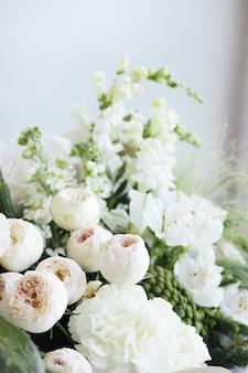 灰色の背景の側面図に白いバラとユーカリのウェディングブーケ。花嫁の朝の準備。スタイリッシュなヨーロッパの結婚式の日の詳細。