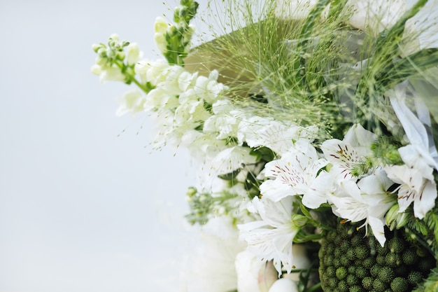 灰色の背景に白いバラとユーカリのウェディングブーケ花嫁の朝の準備...