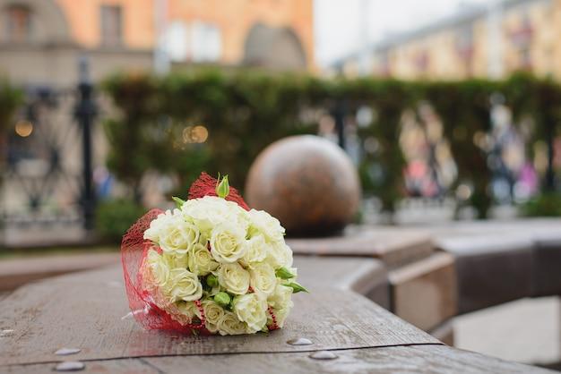 白いバラのウェディングブーケが街のベンチに横たわっています