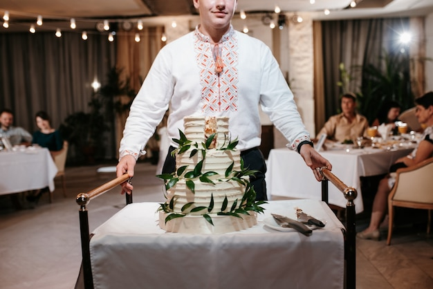 テーブルの上のいくつかの層のウエディングケーキはウェイターによって運ばれます