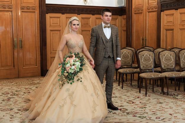 Свадебная церемония. загс. молодожены подписывают документ о браке. молодые пары подписывают документы о браке.