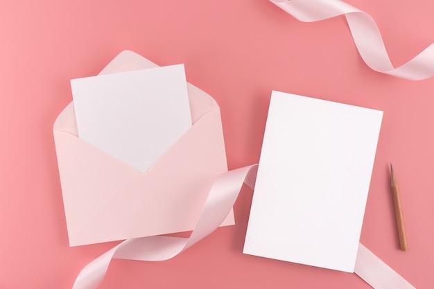 結婚式のコンセプト。結婚式の招待状、ピンクの背景にリボンと装飾が付いています。