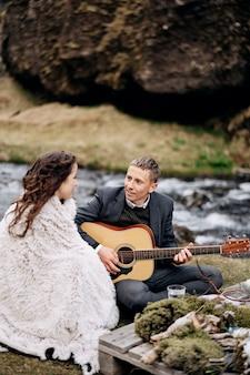 結婚式のカップルが結婚式のディナーのためにテーブルで山の川の岸に座っています
