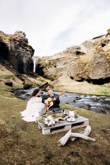 Свадебная пара сидит на берегу горной реки за столом для свадебного обеда.
