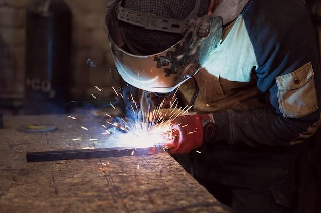Сварщик, который работает со сваркой металла в защитной маске и искры.