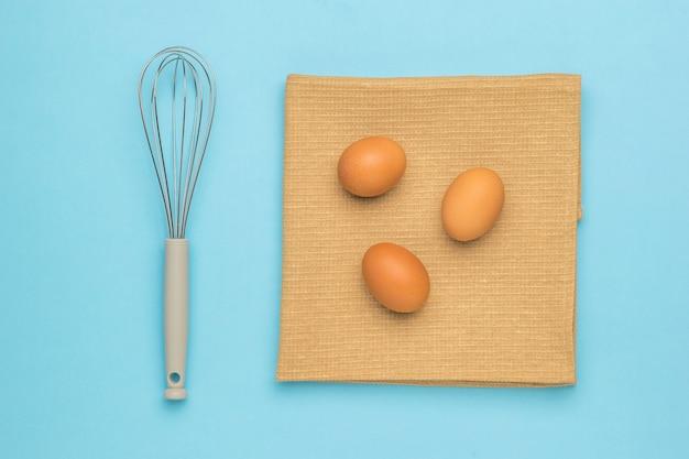 青い表面の布に泡だて器と卵3個。天然物および厨房機器。