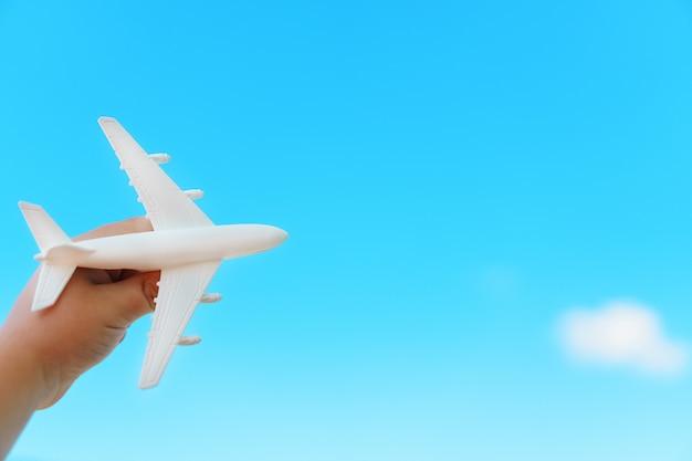 青い空を背景に子供の手に白い飛行機