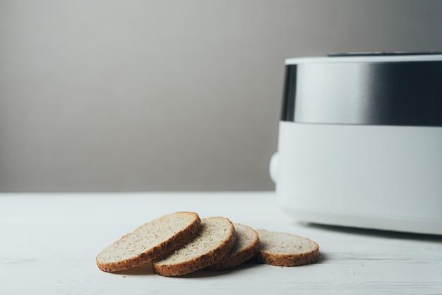 흰색과 은색 토스터는 옆에 빵 조각이있는 흰색 나무 테이블에 앉아 있습니다.