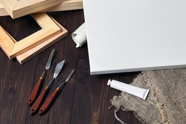 Белый чистый холст с подрамниками и мастихином на коричневом деревянном столе