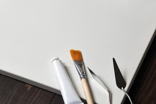 ストレッチャー、パレットナイフ、合成ペイントブラシ、オイル付きチューブに白い空白のコットンキャンバス