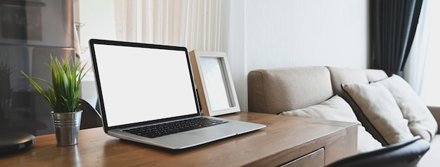흰색 빈 화면 컴퓨터 노트북은 편안한 방에있는 나무 테이블에 걸고있다.