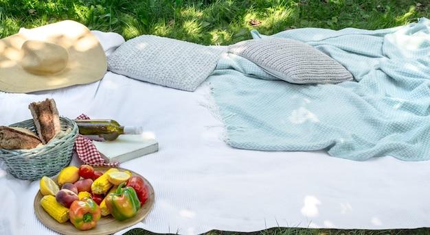 緑の草の上の白い毛布。ピクニックのコンセプト。