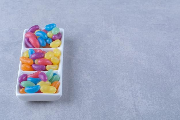 Белая доска, полная разноцветных конфет на серой поверхности