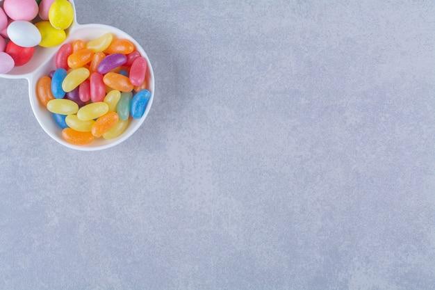 灰色の表面にカラフルな豆菓子でいっぱいのホワイトボード