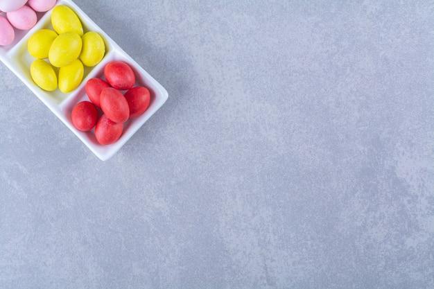 회색 테이블에 다채로운 콩 사탕으로 가득 찬 화이트 보드.