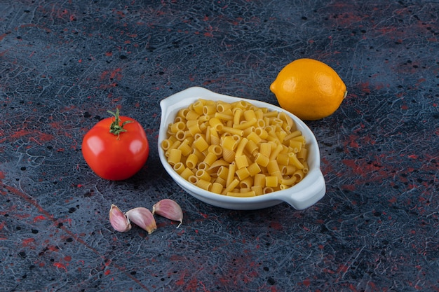 Белая доска сырых макарон со свежими красными помидорами и лимоном на темной поверхности.