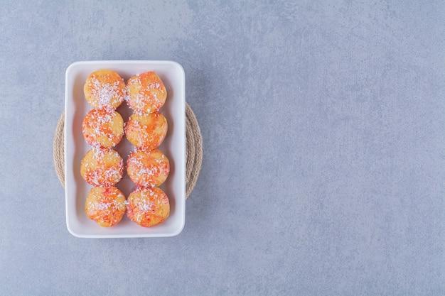 Белая доска круглого желтого печенья с посыпкой.