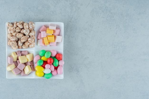 흰색 표면에 마시맬로와 화려한 사탕과 화이트 보드