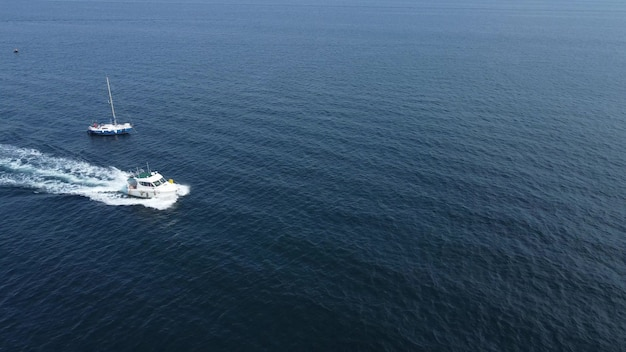 하얀 배 한 척이 푸른 바다의 파도를 빠른 속도로 질주하고 있습니다.