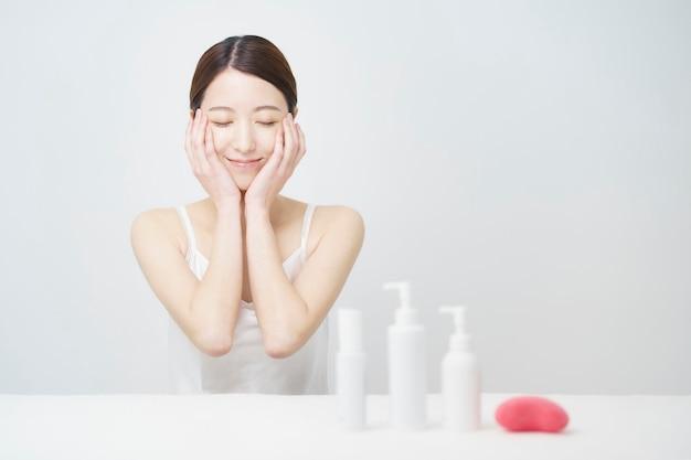 スキンケアのために顔に触れる女性の白いボトル