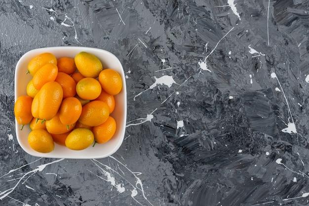 신선한 cumquat 과일이 가득한 흰색 그릇이 대리석 테이블 위에 놓여 있습니다.