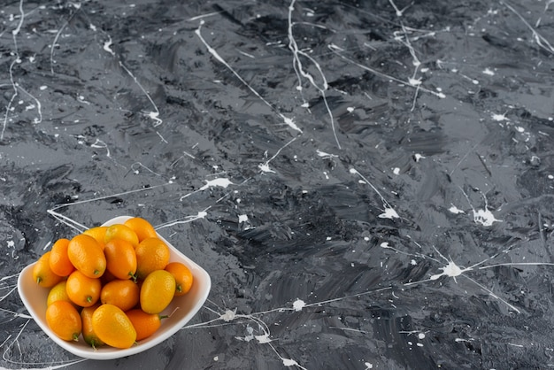 大理石のテーブルの上に置かれた新鮮なキンカンの果実でいっぱいの白いボウル。