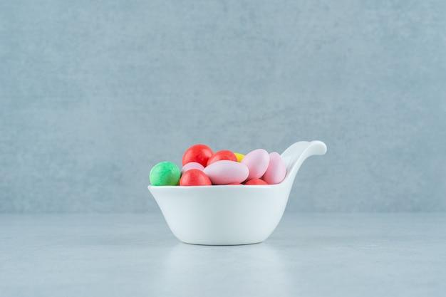 흰색 배경에 둥근 달콤한 다채로운 사탕으로 가득 찬 흰색 그릇. 고품질 사진