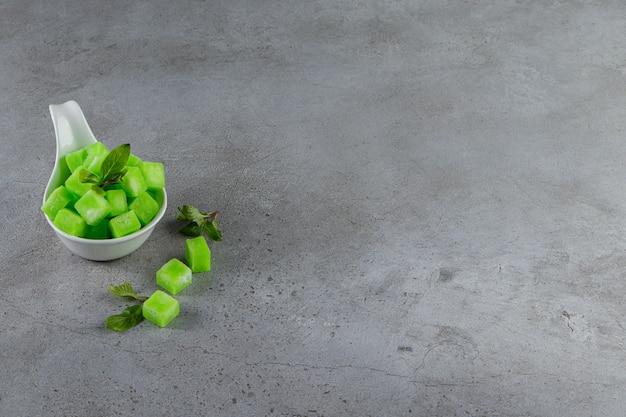 민트와 달콤한 녹색 사탕으로 가득한 흰색 그릇은 돌 테이블에 나뭇잎.