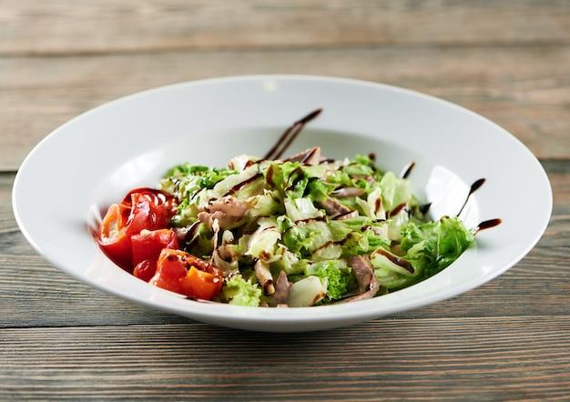 木製のテーブルに白いボウル。チキン、パプリカ、レタスの葉の軽い野菜サラダが付いています。美味しくて美味しそう。