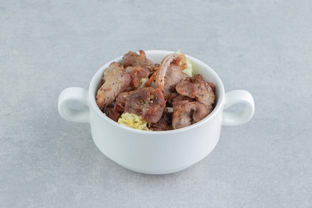 Белая миска с жареным вкусным мясом.