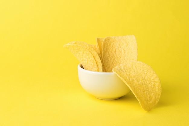 노란색 배경에 감자 칩이 있는 흰색 그릇. 인기있는 감자 요리.
