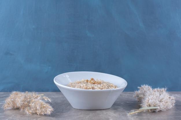 Белая миска с вкусной полезной овсяной кашей на завтрак.