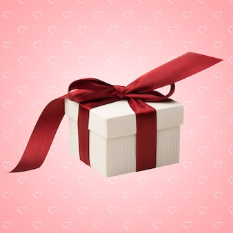 ハートとピンクの抽象的な背景に赤いリボンの弓で結ばれた白いボックス