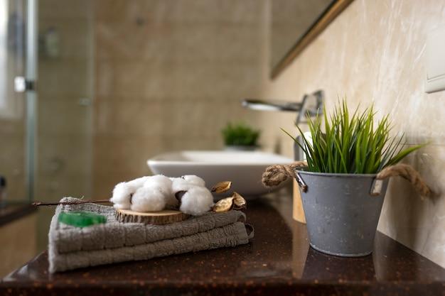 Белая веточка хлопка лежит на хлопковом полотенце в современной ванной комнате.