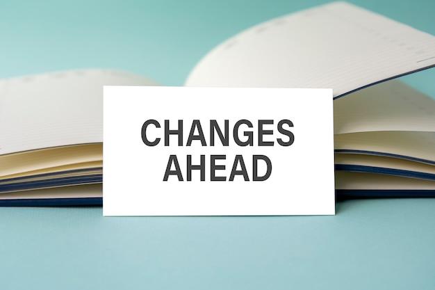 開いている日記を背景に、変更先のテキストが書かれた白い名刺が机の上に立っています。焦点が合っていない