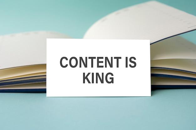 内容が書かれた白い名刺は、開いた日記を背景に机の上に立っている王様のテキストです。焦点が合っていない