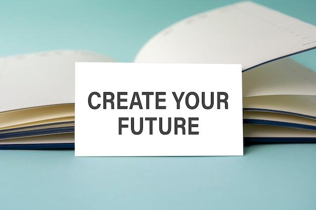 開いた日記を背景に、create yourfutureのテキストが書かれた白い名刺が机の上に立っています。焦点が合っていない