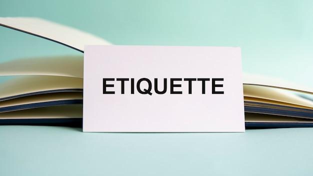 開いた日記を背景に、etiquetteのテキストが書かれた白い名刺が机の上に立っています。焦点が合っていない