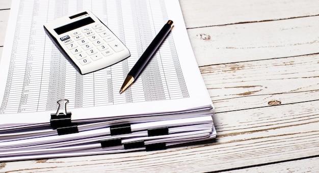 白い電卓とペンは、軽い木製のテーブルの上のドキュメントのスタックに横たわっています