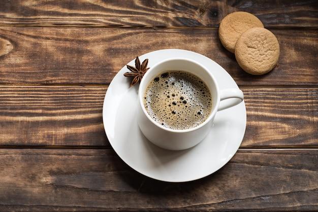 Белая шапочка кофе и аниса на маленькой тарелке с двумя пирожными