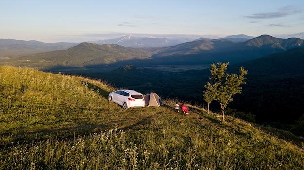 Белая машина стоит на склоне на фоне красивых зеленых гор в адыгее.