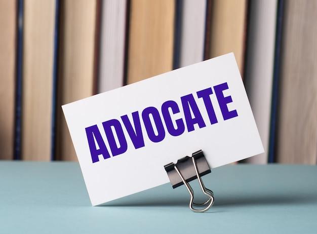 Белая карточка с текстом advocate стоит на зажиме для бумаг на столе на фоне книг. расфокусировать
