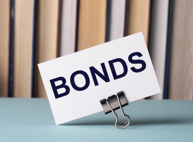 Белая карточка с текстом облигации стоит на зажиме для бумаг на столе на фоне книг. расфокусировать