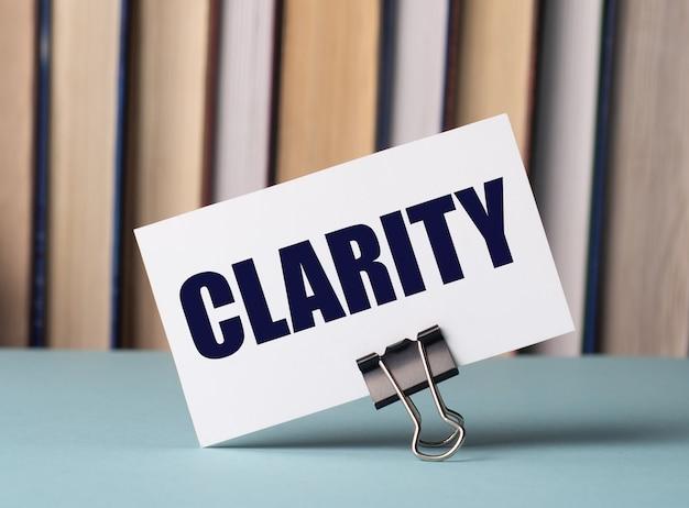 本を背景にしたテーブルの上の紙のクリップの上に、clarityというテキストが書かれた白いカードが立っています。焦点ぼけ