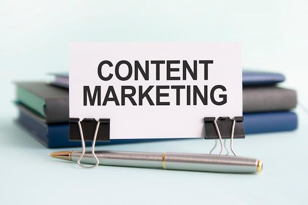 Белая карточка с текстовым контент-маркетингом стоит на зажиме для бумаг на столе на фоне книг. выборочный фокус