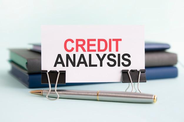 本の背景にテーブル上の紙のクリップの上にテキストクレジット分析の白いカードが立っています。セレクティブフォーカス
