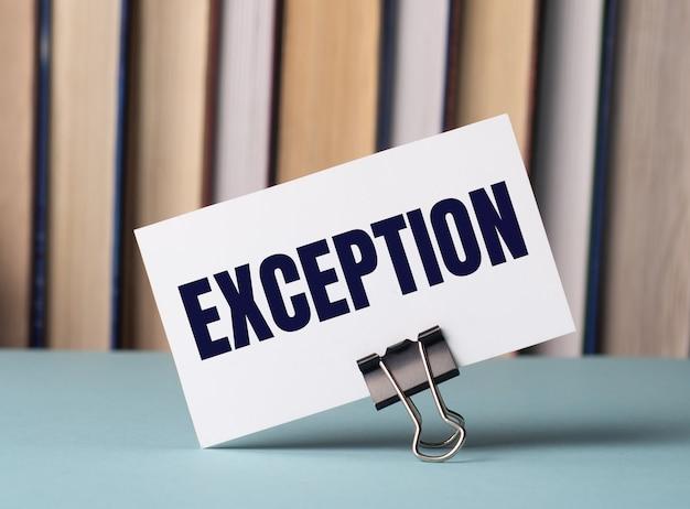 Белая карточка с текстом исключение стоит на зажиме для бумаг на столе на фоне книг. расфокусировать