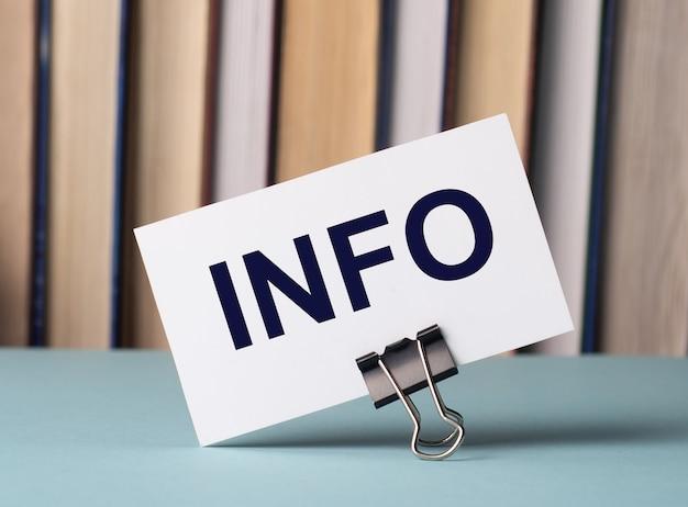 Белая карточка с текстом info стоит на зажиме для бумаг на столе на фоне книг. расфокусировать