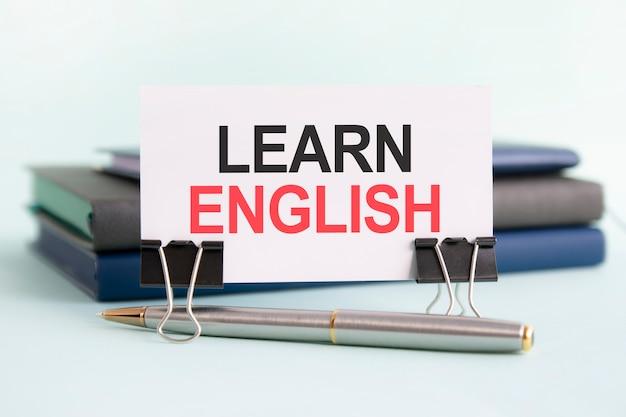 Белая карточка с текстом учить английский стоит на зажиме для бумаг на столе на фоне книг. выборочный фокус