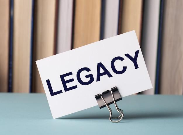 本の背景にテーブルの上の紙のクリップの上に「legacy」というテキストが書かれた白いカードが立っています。焦点ぼけ